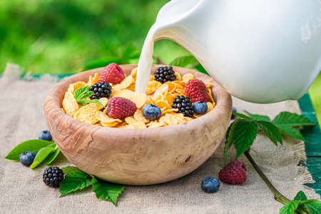 Pouring milk into corn flakes with berry fruits
