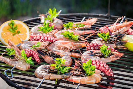 Roasting fresh seafood skewers made of octopus and prawns