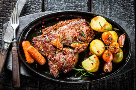 Roasted steak with vegetables and herbs on burned table