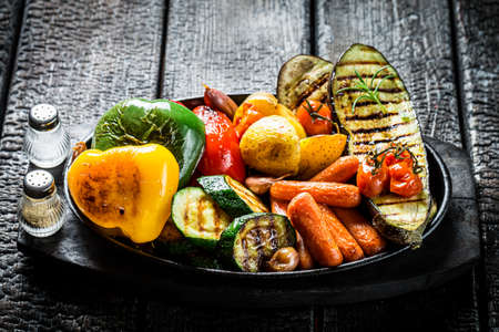 Grilled mix of vegetables on barbecue dish on burning table