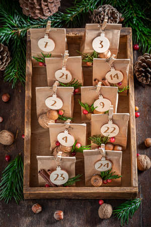 Original Christmas Advent Calendar stacked in a wooden drawer on wooden table