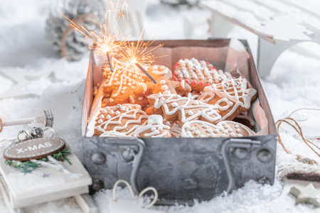 Cookies for Christmas surrounded by Christmas decorations and sparklers on snowy table