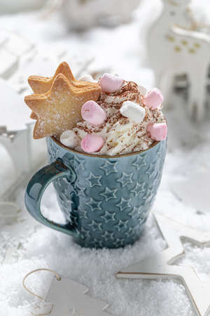 Tasty and warming up cocoa with blue scarf for Christmas on snowy table