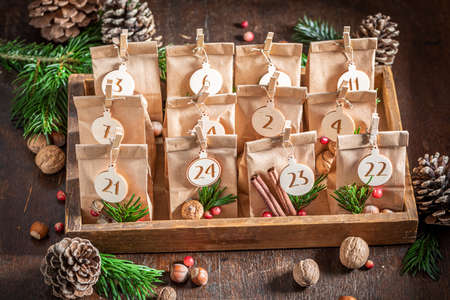 Original Christmas Advent Calendar made of paper bag and clip on wooden table