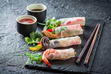 Tasty spring rolls made of fresh vegetables on black rock