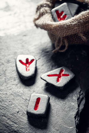 Closeup of runic stones with red sign based on futhark alphabet