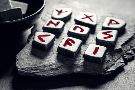Closeup of magic rune stones with red signs based on futhark alphabet