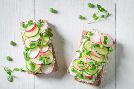 Fresh sandwich with creamy cheese, peas and radish on white table