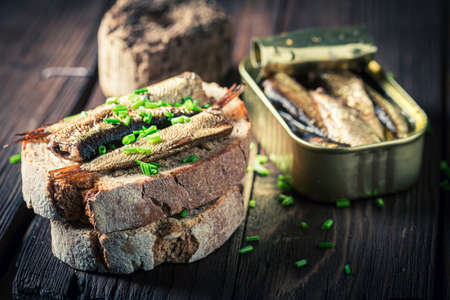 Closeup of sardines sandwich with as quick snack on wooden board