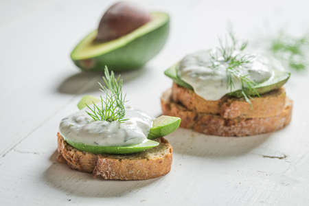 Sandwich with avocado, dill and tzatziki sauce on white table