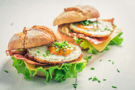 Delicious burger with fried egg, bacon and cheese on white table