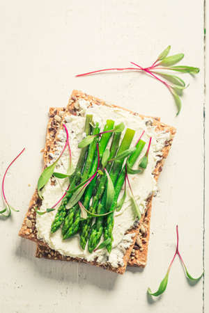 Tasty sandwich with asparagus and fromage cheese on white table 版權商用圖片