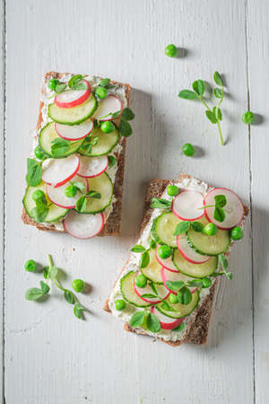 Tasty sandwich with creamy cheese, peas and radish on white table