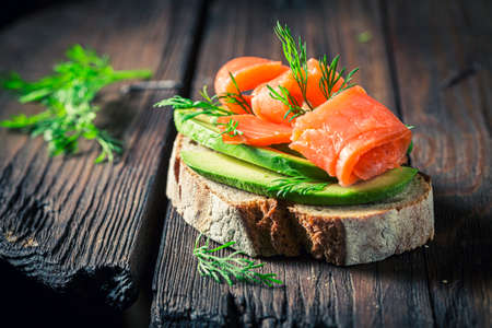 Tasty bread with avocado, salmon and dill on wooden board