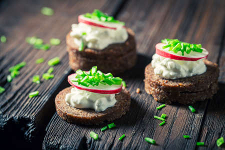 Closeup of sandwich with pumpernickel bread, chive and cottage cheese on wooden table 版權商用圖片