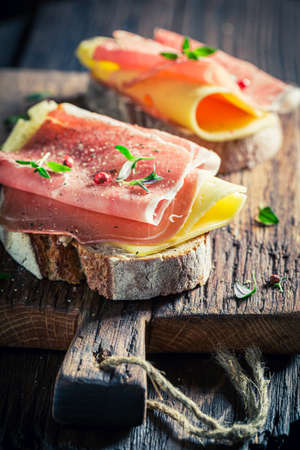 Tasty sandwich with ham, cheese and pepper for breakfast on wooden board