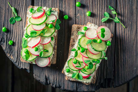 Spring sandwich with radish, creamy cheese and peas on wooden table
