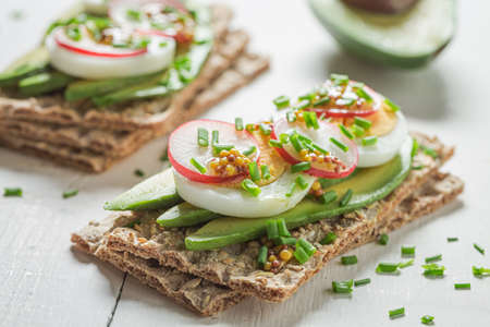Fresh and healthy sandwich with avocado, radish and eggs on white table