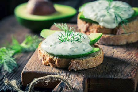 Spring and healthy sandwich with avocado and tzatziki sauce on wooden board Stok Fotoğraf