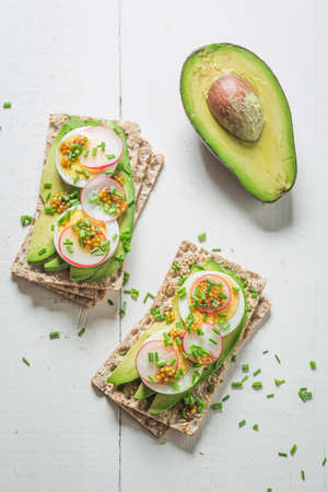 Spring and healthy sandwich with avocado and eggs on white table Stok Fotoğraf