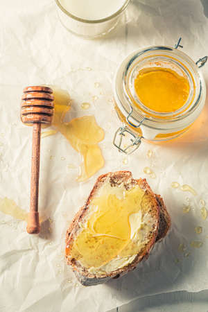 Delicious honey sandwich made of wholegrain bread on baking paper