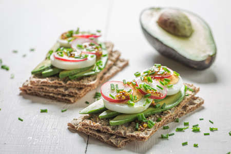 Closeup of sandwich with avocado and eggs on white table
