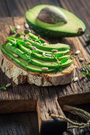 Tasty sandwich with avocado, herbs and sunflower seeds on wooden board
