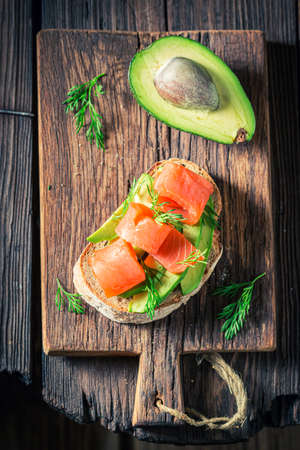Tasty bread with salmon, dill and avocado on wooden board 版權商用圖片