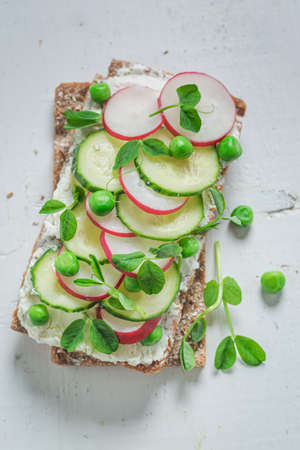 Spring sandwich with creamy cheese, peas and radish on white table