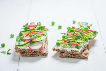 Spring sandwich with creamy cheese on crispy bread on white table