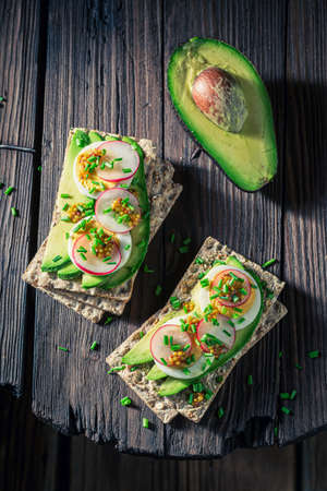 Top view of sandwich with avocado, radish and eggs