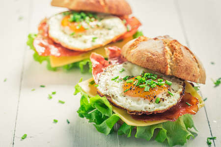 Delicious burger with bacon, fried egg and chive on white table 版權商用圖片