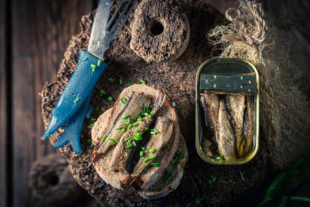 Fresh and delicious sardines sandwich with as quick snack on wooden board