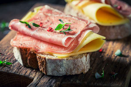 Fresh sandwich with ham, cheese and pepper for breakfast on wooden board 版權商用圖片