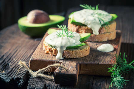 Closeup of sandwich with avocado and tzatziki sauce on wooden board