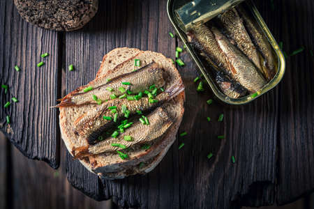 Healthy and fresh sardines sandwich with with chive on wooden board