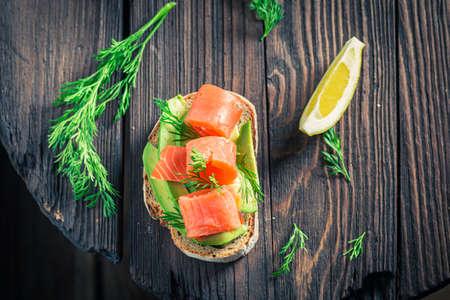 Fresh bread with avocado, salmon and dill on wooden board 版權商用圖片