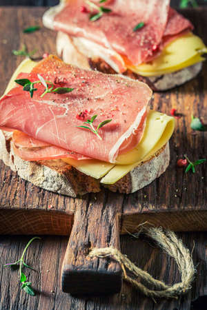 Delicious sandwich with cheese, ham and herbs for breakfast on wooden board 版權商用圖片