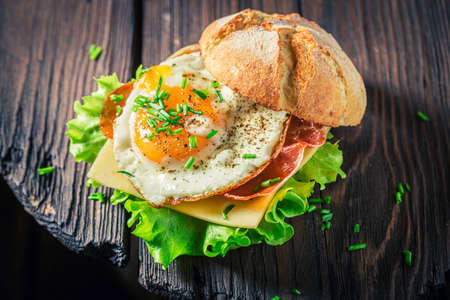Delicious burger with lettuce, fried egg and bacon on white table 版權商用圖片