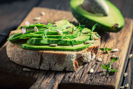 Sandwich with avocado, herbs and sunflower seeds on wooden board