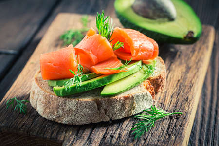 Healthy bread with salmon, dill and avocado on wooden board