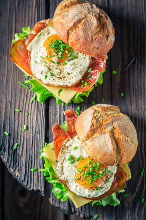 Tasty burger with bacon, fried egg and chive on white table 版權商用圖片
