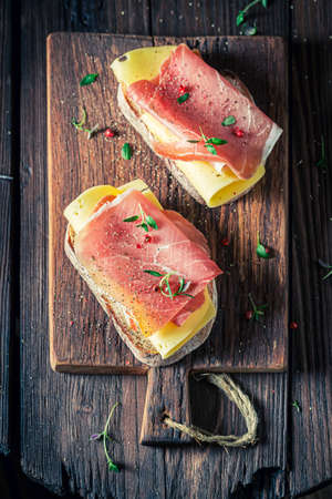 Delicious a piece of bread with ham, cheese and pepper on wooden board 版權商用圖片