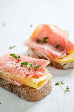 Tasty a piece of bread with cheese, ham and herbs on wooden board 版權商用圖片