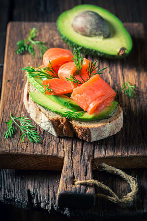 Fresh bread with salmon, dill and avocado on wooden board 版權商用圖片