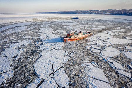 Icebreakers crushing ice on Vistula River near Plock, 2020-02-18, Poland, aerial view