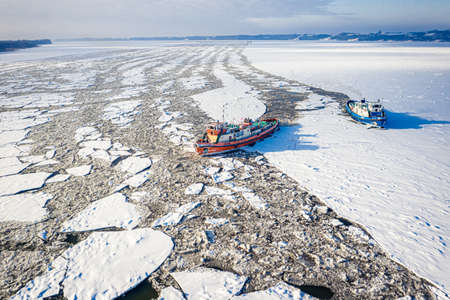Icebreakers floating on frozen Vistula crush the ice, 2020-02-18, Poland, aerial view