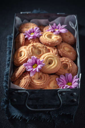 Delicious round butter cookies in an old metal box on dark table