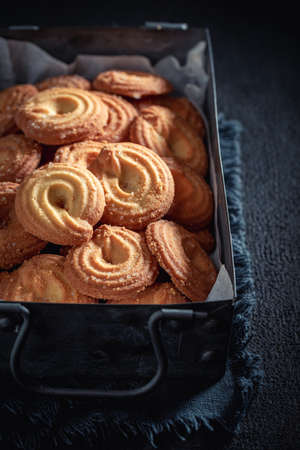Homemade danish cookies as crunchy and vanilla snack on dark table