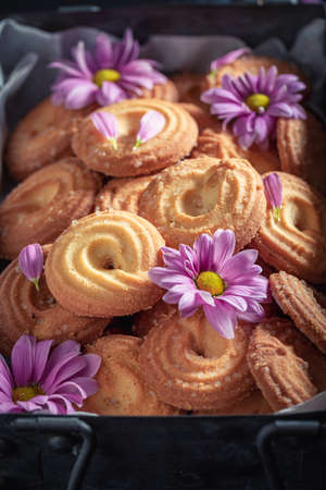 Sweet round butter cookies in an old metal box on dark table